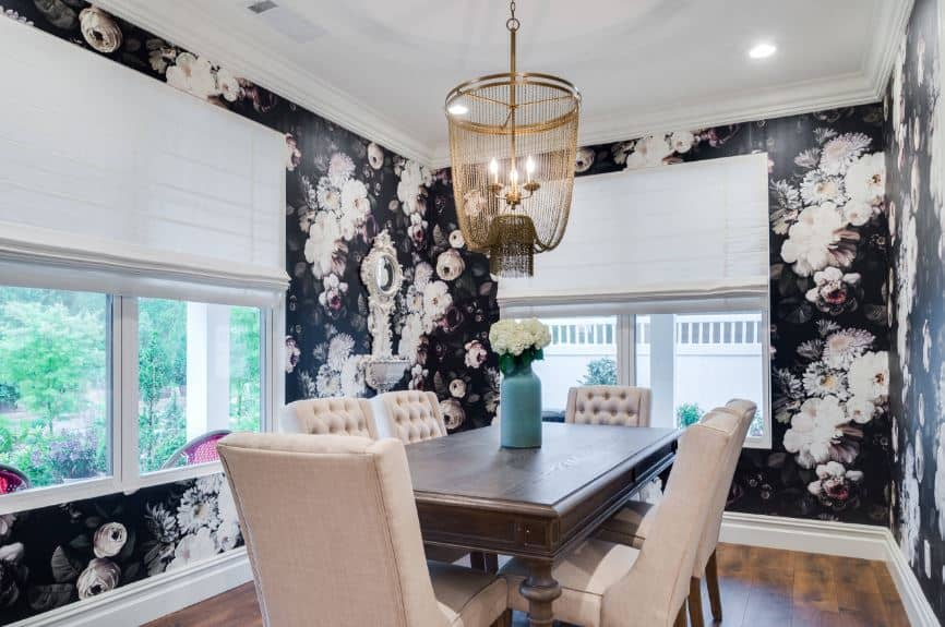 The black walls are filled with images of flowers that pair nicely with the white ceiling and beige cushioned chairs surrounding the wooden table.