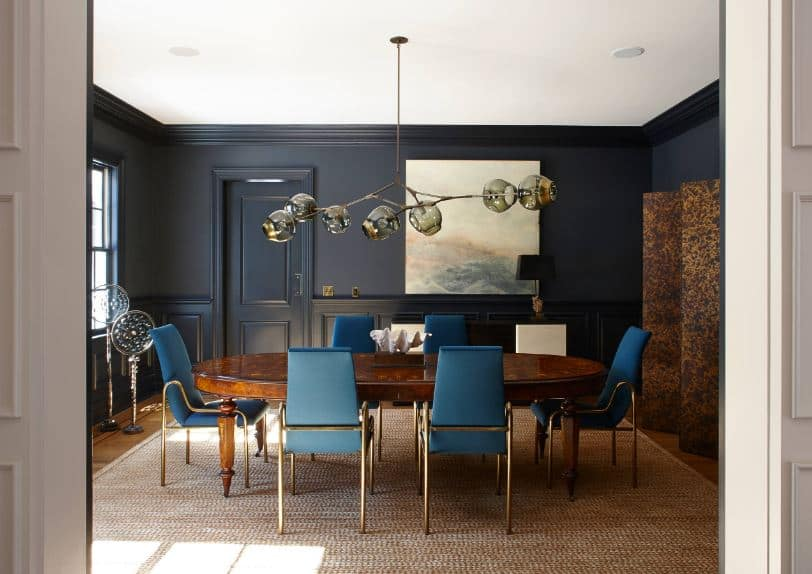 The blue cushions of the dining chairs around the wooden table stand out against the black walls that have consistent black wainscoting.