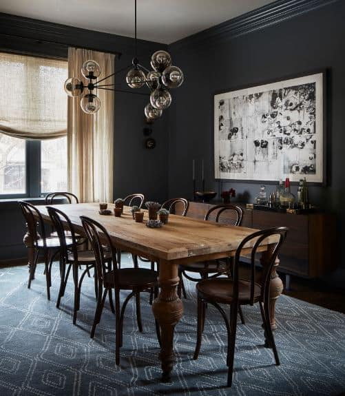 The black walls are accented with a wall-mounted artwork that stands out against the black background. This is complemented by a blue patterned area rug under the wooden table surrounded by wooden chairs.