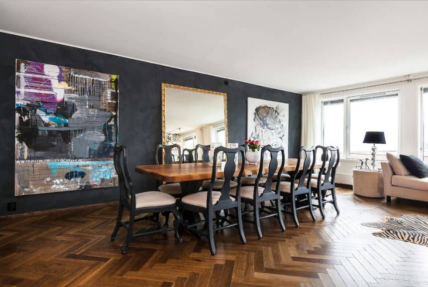 The hardwood flooring matches with the wooden top of the dining table that is surrounded by elegant dark gray chairs that in turn complement the black walls with massive artworks.