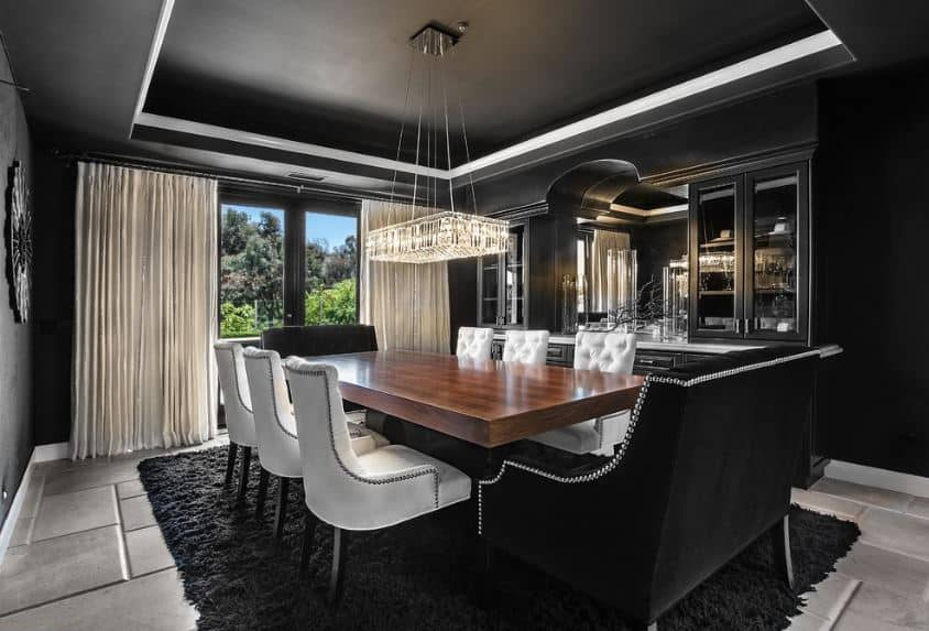 The charming black velvet cushioned chairs at the heads of the wooden dining table are perfectly matched with the black walls and tray ceiling.