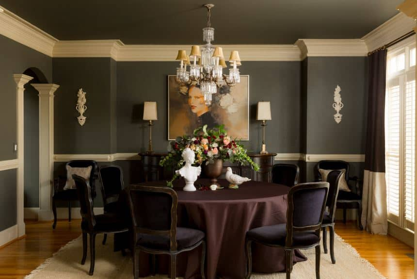 The black walls that are adorned with a classic painting of a woman is a perfect match for the black velvet cushions of the dining chairs surrounding the circular dining table covered in dark maroon cloth.