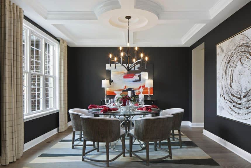 The white coffered ceiling has a circular coffer in the middle that reflects the circular glass table paired with gray armchairs that stand out against the black walls.