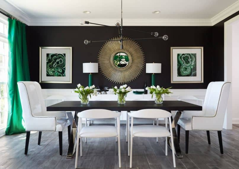 The lovely pairing of green elements on the black walls is well executed. This is then brightened up by the white wainscoting paired with white dining chairs.