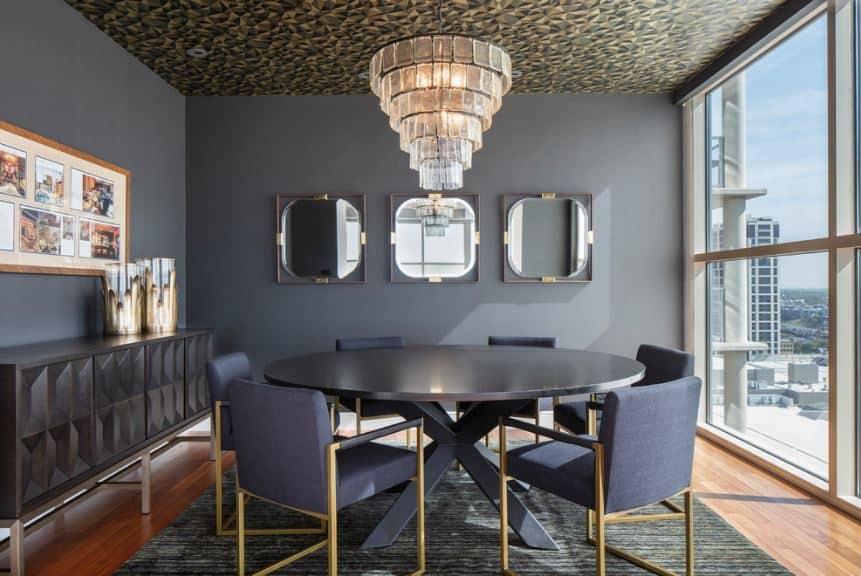 The black walls are accented with a pitch-black circular dining table that matches the console table with cabinets on the side.
