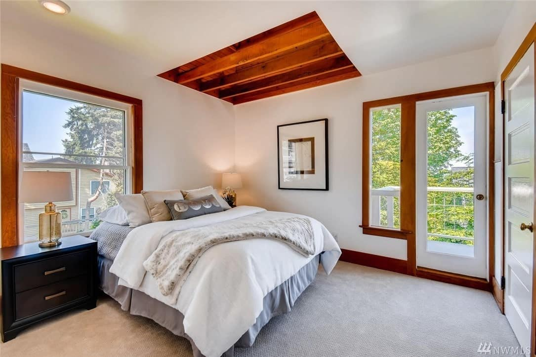 The white carpeted floors match with the white walls and white ceiling that has a section fitted with exposed wooden beams. These wooden beams have the same hue as the frames of the window and glass door. A simple wall-mounted artwork hangs beside the bed that has gray and white bedsheets.