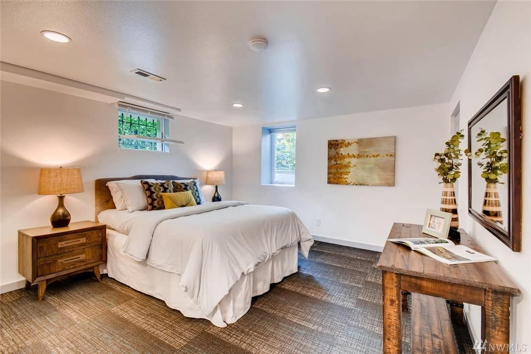 The flooring of this Craftsman-Style bedroom has a patterned wooden design that matches with the console table and bedside drawers flanking the bed. A pair of brass modern lamps illuminate the white ceiling and walls with a wall-mounted artwork that has a plant-like depiction on it.