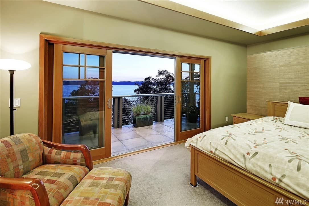The brilliant tray ceiling has green hues bordering it that melds into the walls where massive sliding glass doors shines natural light on the carpeted flooring. The massive wooden bed has the same wooden hue as the bedside table and frames of the glass doors.