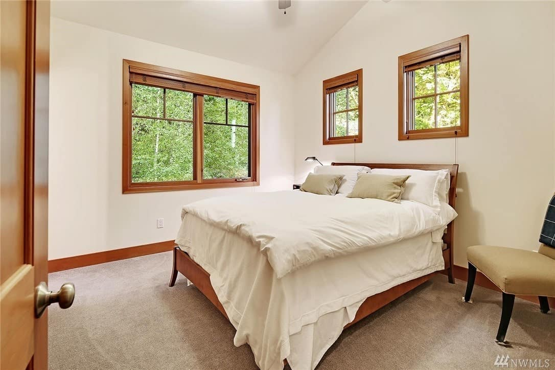 The flooring of this Craftsman-Style bedroom is covered with a gray carpet that is bordered with a wooden strip that matches with the frames of the bed, windows, and door. The white bedsheets match well with the white walls and white cathedral ceiling.