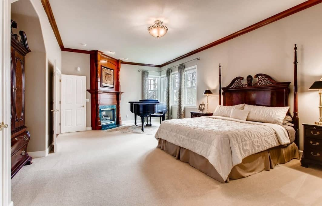 The elegant headboard of the massive bed has a redwood finish that pairs well with the wooden structure that houses the fireplace between the door and grand piano. This redwood hue is also applied to the molding of the white ceiling that has a semi-flush mount lighting in the middle that shines over the carpeted floor.