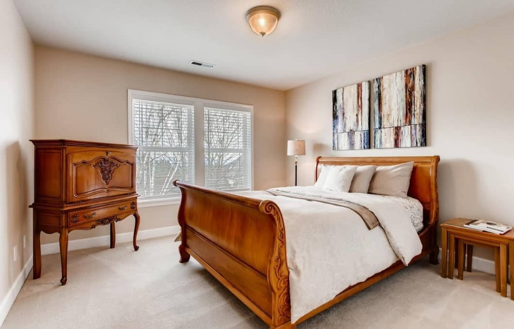 A beautiful wooden French dresser stands at the corner of this Craftsman-Style bedroom beside the window. The dresser matches the design and wooden finish of the bed with a curved wooden headboard that contrasts with the white bedsheets and carpeted flooring.