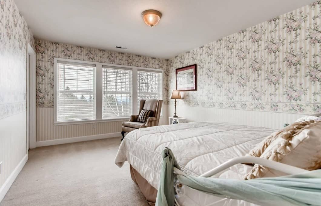 The walls of this Craftsman-Style bedroom is covered with a chic floral wallpaper that melds well with the white ceiling and white carpeted flooring. Across from the bed is a lovely reading area with a single sofa beside the windows and a tabletop lamp.