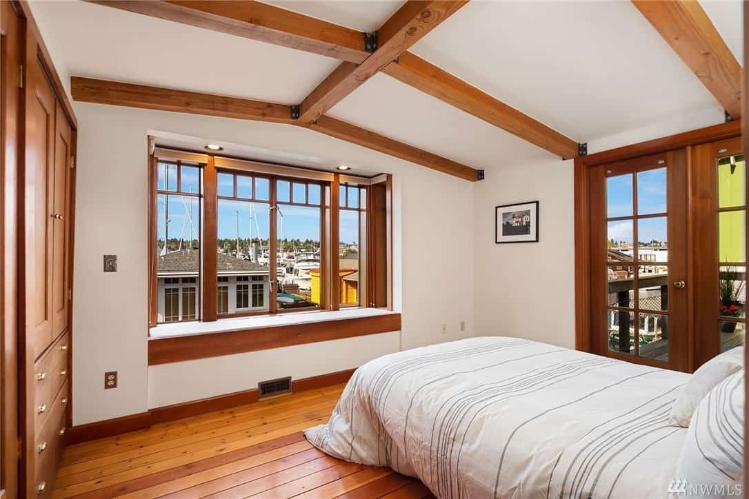 The bed with white sheets is facing the windows in this Craftsman-Style bedroom. The windows have a frame that has wooden hues matching with the frame of the French doors and built-in cabinets as well as the hardwood flooring and exposed wooden beams of the cathedral ceiling.