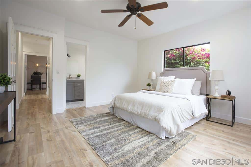 The dark ceiling-mounted fan stands out against the whiteness of the ceiling and the walls that match with the white bedsheets. The light gray tones of the headboard match with the color of the patterned rug at the foot of the bed over the hardwood flooring.