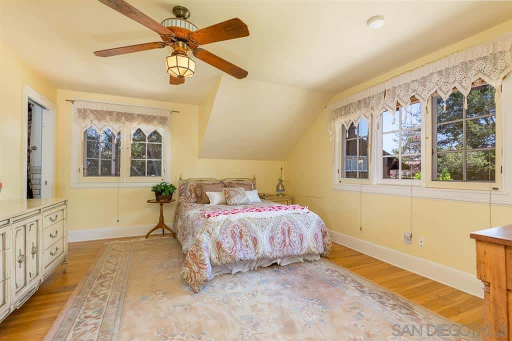 The hardwood flooring of this beige-walled Craftsman-Style bedroom is covered by a massive worn patterned rug that matches the bedsheets. Lovely patterns of lace lines the French windows that have a white frame plays well with the beige ceiling.