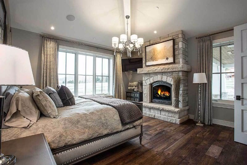 The centerpiece of this Craftsman-Style primary bedroom is the gorgeous fireplace that has a rough stone housing extending to the white ceiling. There is a framed photo mounted above the fireplace that is illuminated by the modern chandelier. The gray bed matches with the gray walls and contrasts the hardwood flooring.