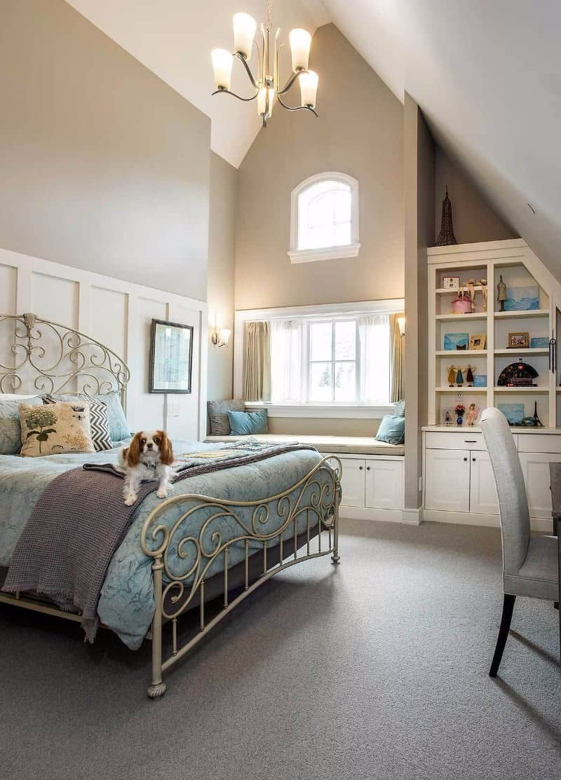 This Craftsman-Style bedroom has a distinctly chic presence in its intricate patterned metal bedframe paired with the colorful bedsheets. A sense of elegance is brought by the sleek chandelier hanging from a high cathedral ceiling. A lovely reading nook is added to the window-side that is fitted with cabinets.