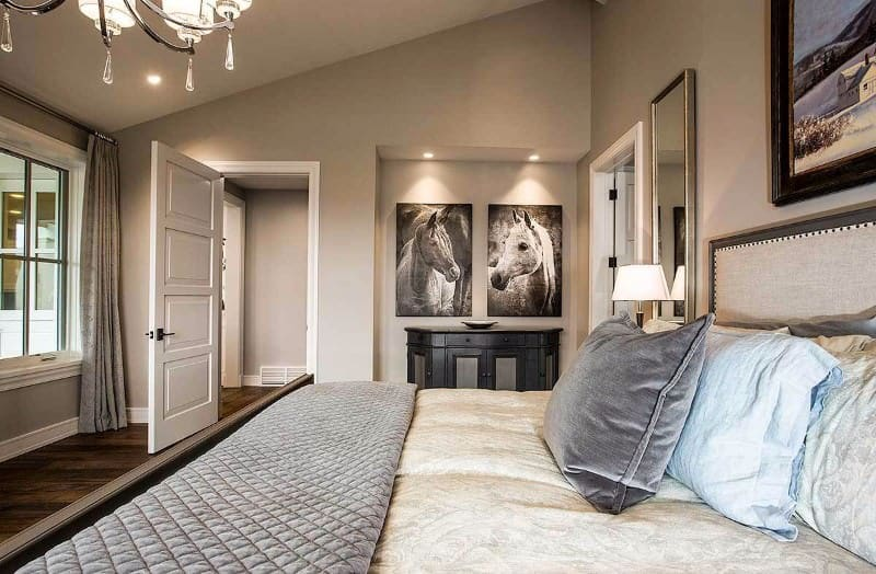 This Craftsman-Style bedroom has a shed ceiling with a gray hue that blends with the gray walls. There are a couple of horse artworks that are mounted above a console table fitted with cabinets and drawers. The massive bed is illuminated by a chandelier above it and a couple of table lamps beside it.