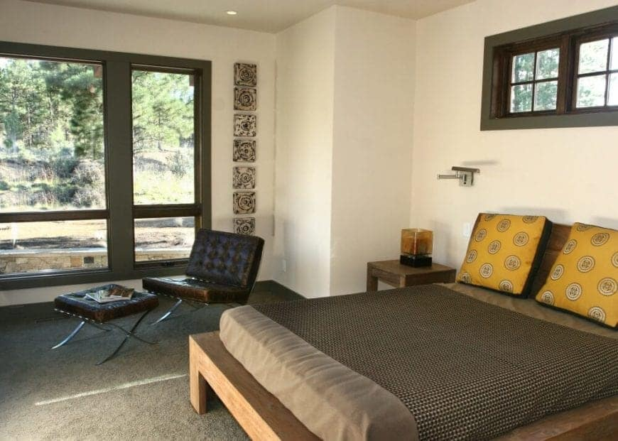 The gray hues dominate this Craftsman-Style bedroom in its gray carpeted flooring, bedsheets and frames of the windows above the bed and beside the leather sofa that serves as a reading area. The platform-style wooden bedframe matches with the wooden bedside tables.