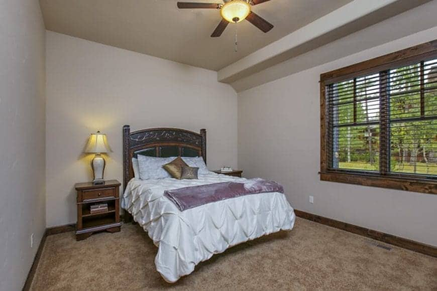 This Craftsman-Style bedroom has a shed ceiling with light hues that blend into the walls and bedsheets. This is contrasted by the carpeted flooring that matches with the wooden headboard, bedside drawers and the frames of the window.