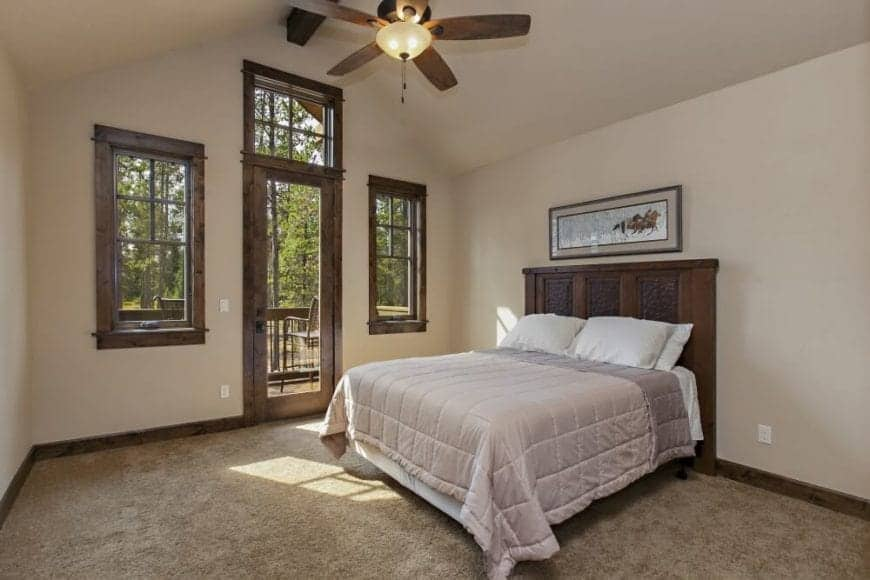 The elegant wooden headboard is a perfect match for the frames of the windows and glass doors. These windows and door provide a nice view of the outside that contrasts with the simple theme of this Craftsman-Style bedroom with cathedral ceiling.