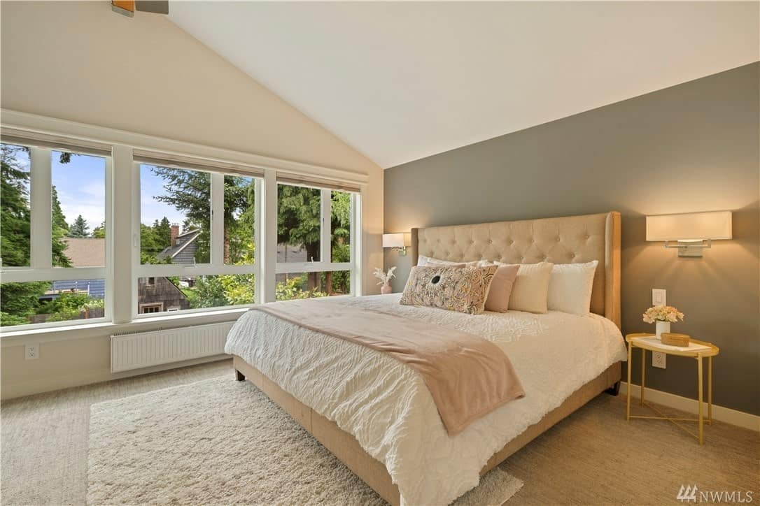 The wall beside the beige bed with a cushioned headboard is dominated by walls that brighten up the white cathedral ceiling and beige walls. This matches with the carpeted flooring. The wall behind the headboard is painted gray and fitted with wall-mounted modern lamps over bedside tables.