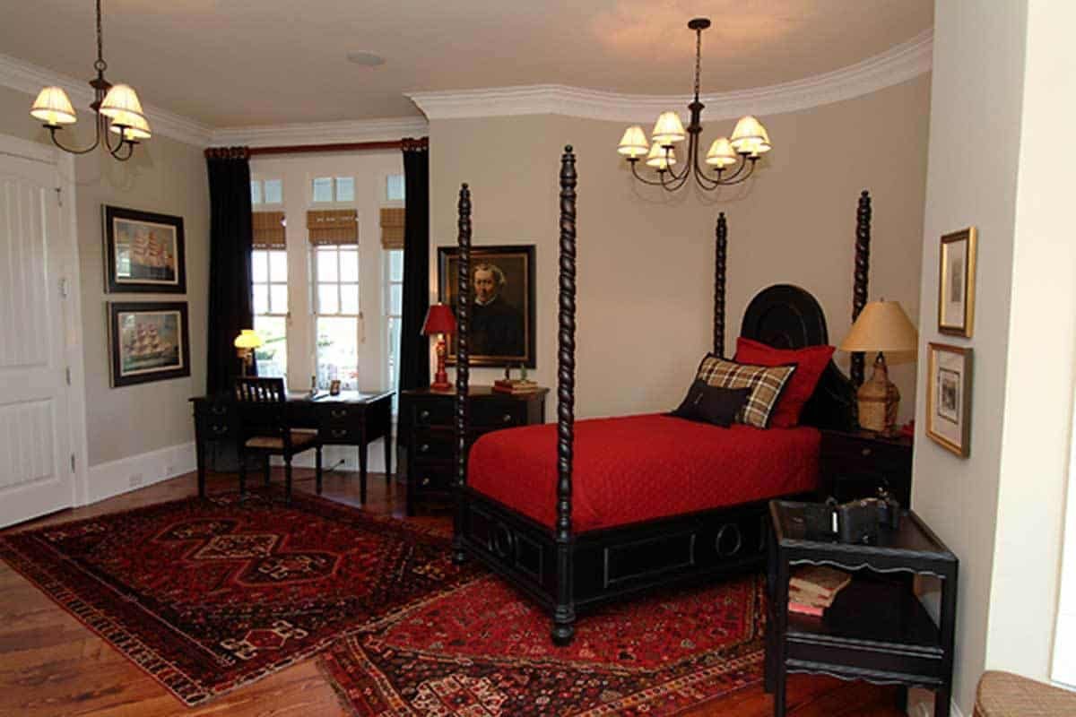 The dramatic red patterned rugs over the hardwood flooring pairs with the red bedsheets that seem to darken the wooden four-poster bed, desk, and drawers beside the bed. This stands in contrast with the beige walls and ceiling where simple chandeliers hang.