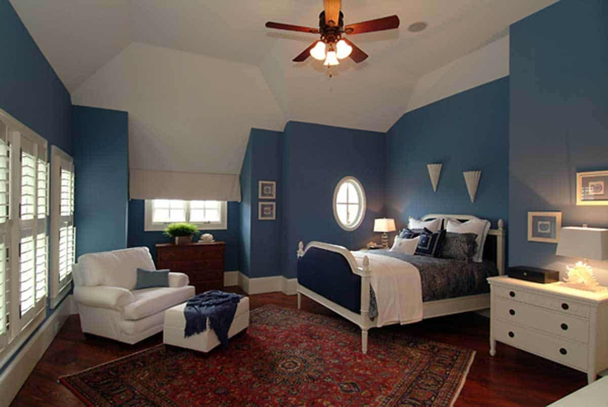 The white vaulted ceiling of this Craftsman-Style bedroom contrasts with the bluish walls that match the dark blue cushions of the wooden bed. There is a white dresser beside the bed that matches the white single sofa beside the shuttered windows.