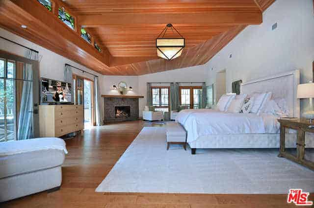 The shed ceiling of this Craftsman-Style primary bedroom has a wooden finish that mirrors the hardwood flooring. The ceiling has an exposed wooden beam that supports the semi-flush lighting with a pyramidal shape. There is a fireplace at the corner with stone borders that stand out against the white walls, bed and area rug.