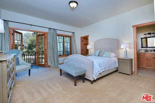 The beige carpeted floors are a good match for the white walls and white ceiling. The bed has a cushioned gray headboard that is flanked by table lamps on bedside drawers. Illumination is provided by the ceiling flush lighting and the natural lights coming in through the glass windows and doors.