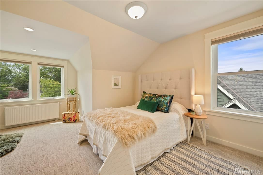 The charming bed has a beige cushioned headboard and placed on a lovely corner by the window and under an irregular white ceiling. The ceiling-mounted flush lighting illuminates the beige walls and carpeted flooring.