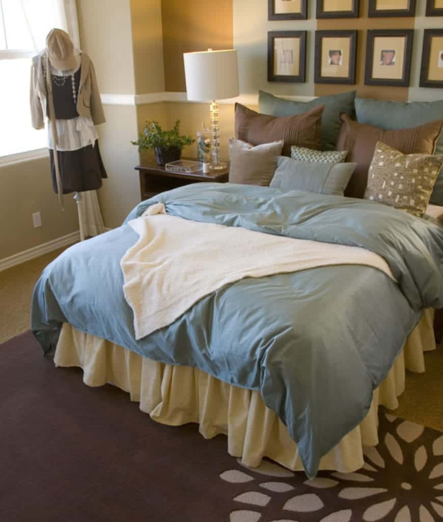 The bed has bluish sheets and multi-colored pillows that contradicts the beige walls and carpeted flooring. At the foot of the bed, there is a brown area rug with a floral pattern. This rug is a good match for the wooden bedside table where a bedside lamp is placed.