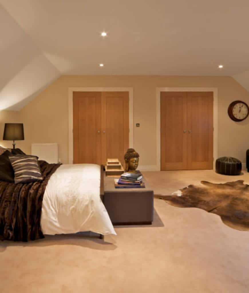 The beige carpeted flooring is accented with an animal hide area rug that matches the bedsheet. There is a rectangular ottoman at the foot of the bed that is adorned with books and a buddha head figurine. The vaulted white ceiling has pin lights that illuminate the beige walls.