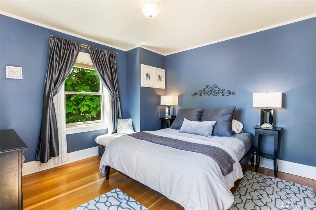 The bluish walls of this Craftsman-Style bedroom is a good contrast to the white ceiling with a white ceiling mounted flush light. The bed with blue pillows are flanked by a pair of wooden bedside table with modern lamps on them. The hardwood flooring is covered with patterned rugs.