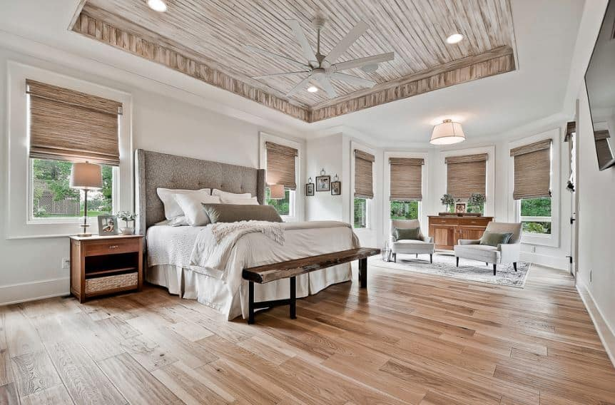 The striped wooden patterns of the tray ceiling match perfectly with the blinds of the multitude of windows lining the white walls of this Craftsman-Style bedroom. The gray cushioned headboard of the white bed contradicts well with the wall and hardwood floor.