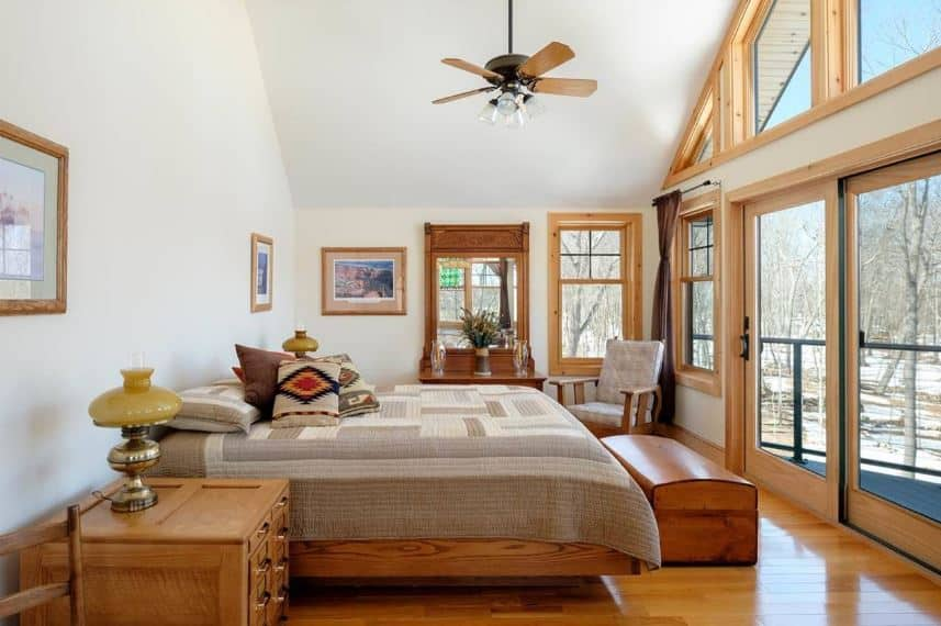 A charming wooden footlocker is placed at the foot of the comfortable wooden bed with gray a patterned bedsheet that contrasts the white walls and white cathedral ceiling. The massive sliding glass doors are topped with glass windows that extend to the ceiling.