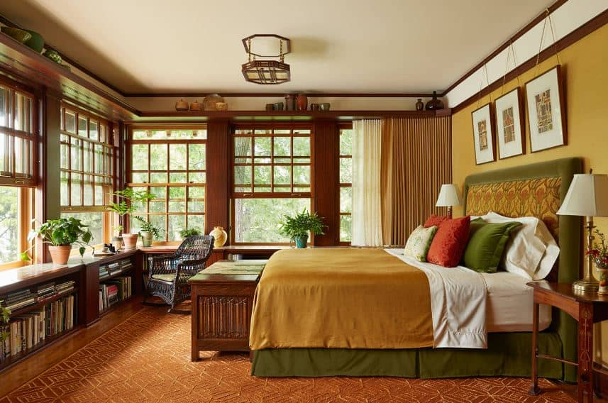 The brown flooring has patterns that match the peculiar semi-flush lighting mounted on the white ceiling. The bed has a green cushioned headboard against a beige wall with framed wall-mounted artworks. Massive French windows dominate the walls across the bed.
