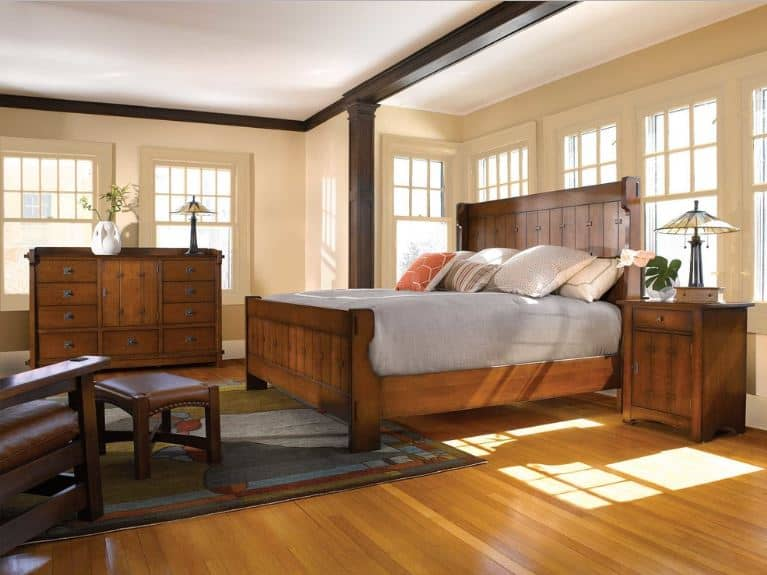 This Craftsman-Style primary bedroom has an immense wooden mission bed against an alcove lined with beige-framed windows. There is a colorful patterned area rug at the foot of the bed that contrasts with the light hues of the hardwood flooring.