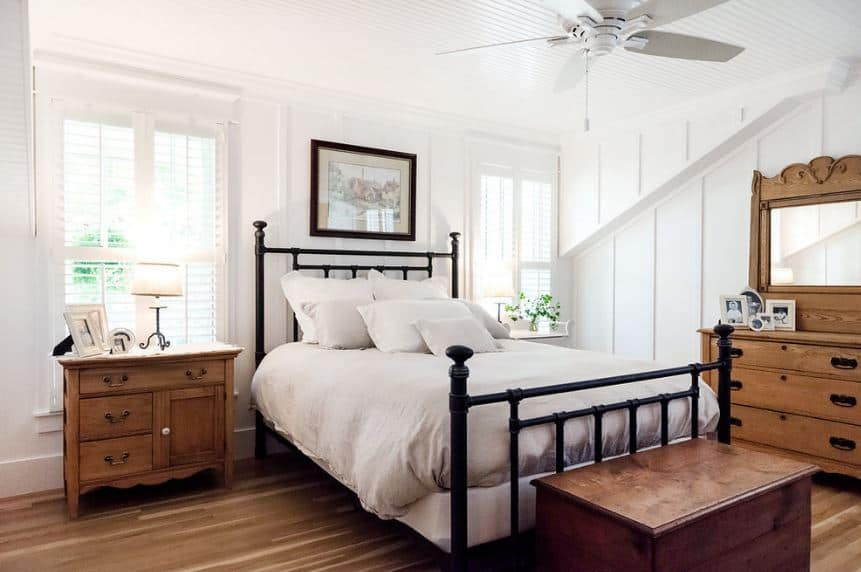 This wrought-iron bed has a dark hue that stands out against the brightness of the walls and ceiling with an equally bright ceiling-mounted fan. The hardwood flooring matches well with the bedside drawer and dresser as well as the footlocker at the foot of the bed.