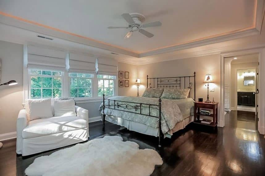 The shiny dark wooden floors are neutralized by the furry white area rug at the foot of the wrought-iron bed. This white area rug is paired with a white cushioned sofa that serves as a reading area beside the French windows and a standing lamp.