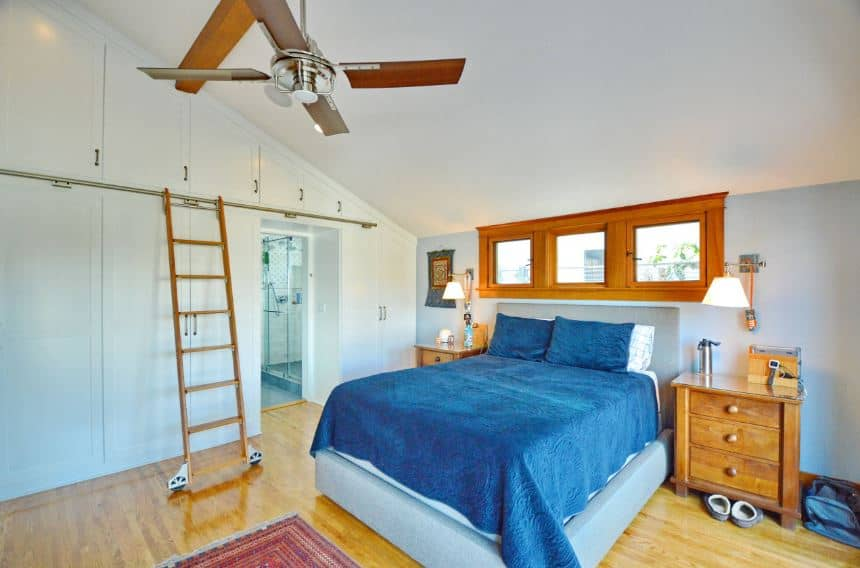 The vertical space of the wall is maximized with built-in cabinets that extend all the way to the white cathedral ceiling. This is paired with a wooden library ladder with rollers. The ceiling has a single exposed wooden beam that supports the ceiling fan. The bluish bed is a perfect match for the hardwood flooring and white walls.