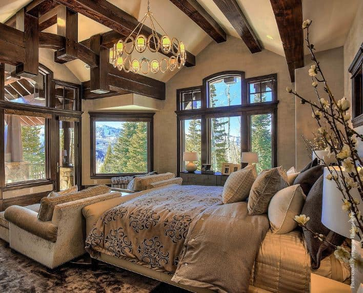 The irregularly vaulted ceiling of this Craftsman-Style primary bedroom has exposed wooden beams with dark wooden hues that mirror the frames of the windows dominating the walls facing the bed. The foot of the sleigh bed has a pair of single sofas that face the windows.