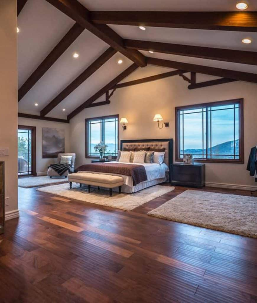 This is a spacious Craftsman-Style primary bedroom that has a cathedral ceiling with exposed wooden beams that mirror the wooden hues of the flooring. Two massive windows flank the cushioned headboard of the bed with a cushioned bench at the foot of it.