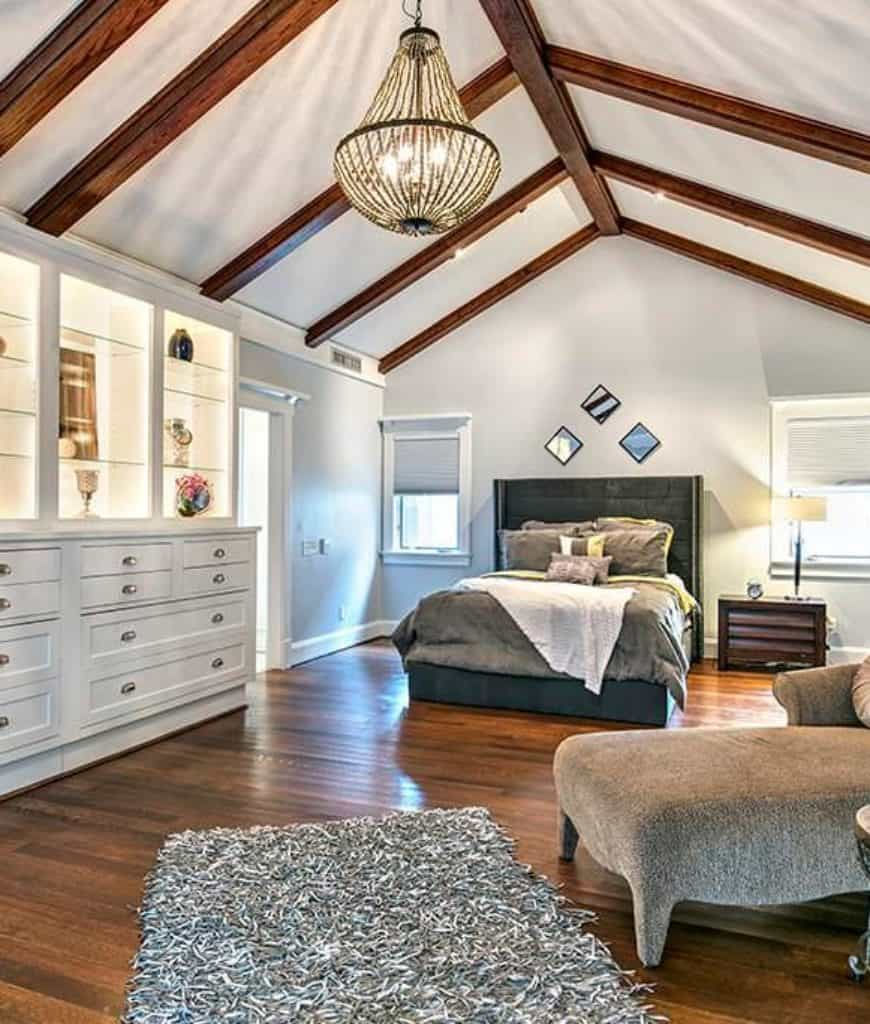 The high cathedral white ceiling has exposed wooden beams that support the large pendant lighting that illuminates the hardwood flooring. The white built-cabinet shows the craftsmanship evident in the wall finish and frames of the windows that flank the bed and its dark headboard.