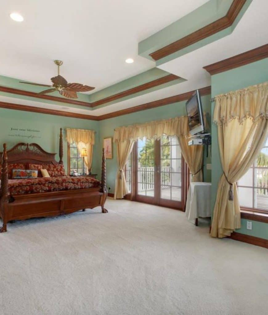 This Craftsman-Style bedroom has a floor covered in white carpet that makes the dark wooden tone of the four-poster bed pop out. The walls are covered in greenish hues that extend to the irregular tray ceiling where a charming fan with leaf-like blades is mounted.