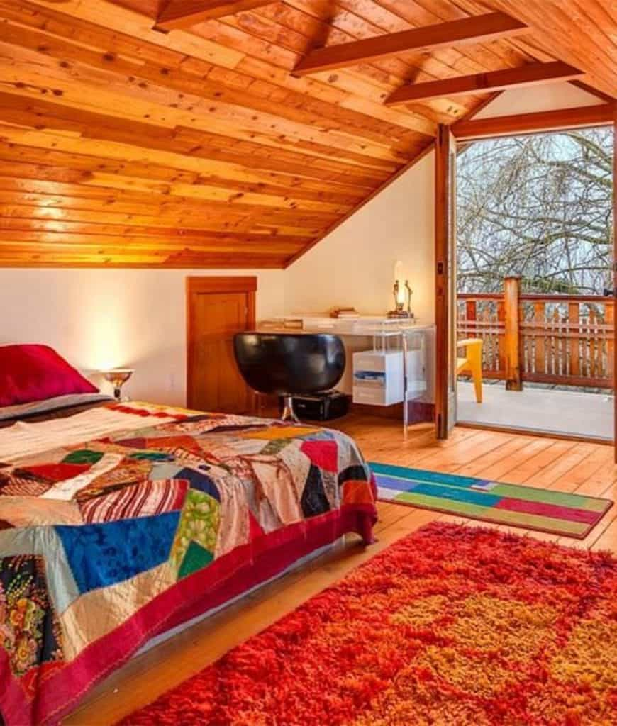 This is a vibrant bedroom with a low cathedral ceiling fitted with exposed beams. This Craftsman-Style bedroom has huge glass doors that open to a balcony that provides natural lighting for the hardwood flooring covered in colorful patterned rugs.