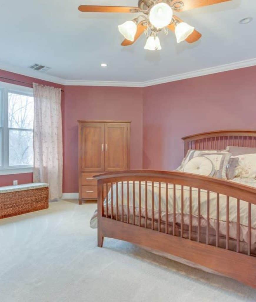 This Craftsman-Style bedroom has lovely pinkish walls that give this bedroom an image of being in a serene painting. The pink walls are sandwiched by white carpeted floors and white ceiling with pin lights on its corners illuminating the simplicity of the wooden bed and cabinet.