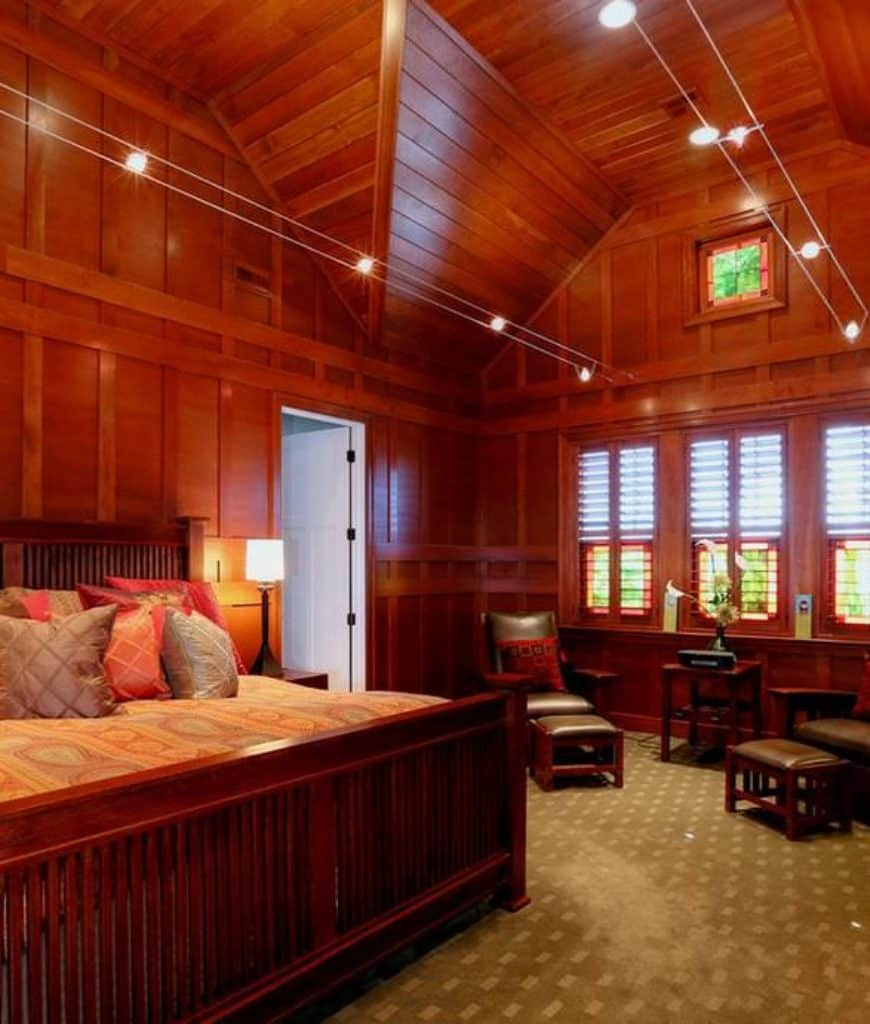 The dominating presence in this Craftsman-Style bedroom is the redwood hues that fill the walls all the way to the high vaulted ceiling. This is also seen in the bedframe and the pair of leather upholstered wooden chairs by the window. This redwood hue is balanced by the light green tone of the patterned carpet of the floor.