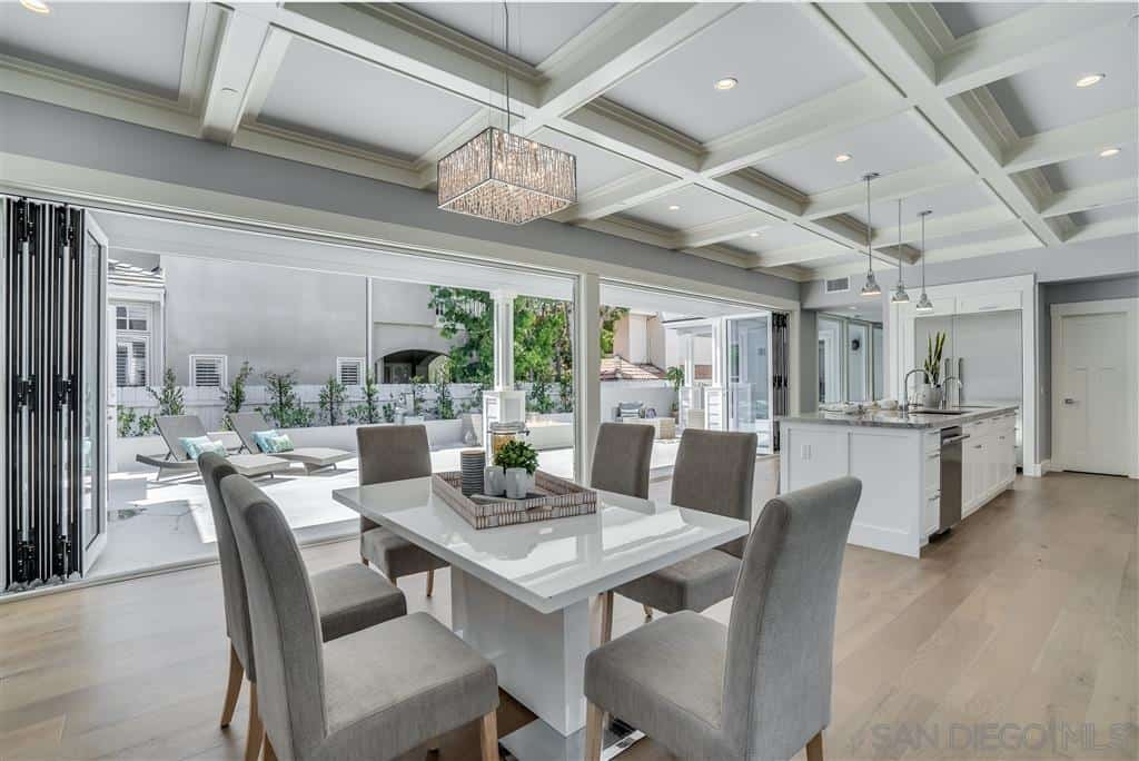 The high coffered ceiling is a good match for the modern white dining table surrounded by cushioned gray Parsons chairs. The grayish tinge of the walls and ceiling serves to give an eye-pleasing effect that is enhanced by the hardwood flooring.