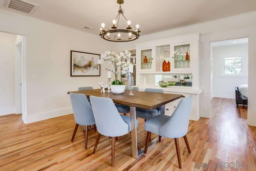 Charming cushioned bluish chairs encircle the modern wood-topped table that is illuminated by the circular chandelier hanging from a white ceiling. The white walls are paired with a wall-mounted artwork and a massive white wooden cabinet that is both functional and decorative.